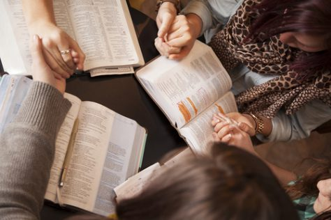 group of women praying together with bibles