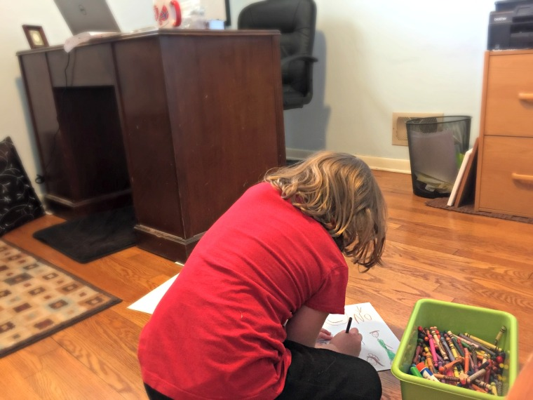 young girl coloring on the floor of her mother's writing office