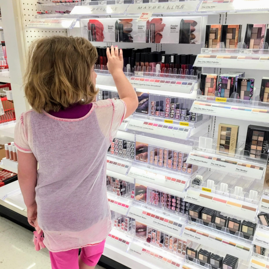 little girl in makeup aisle looking at beauty products